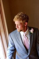 Natural light Groom looking out window of Alma Chapel